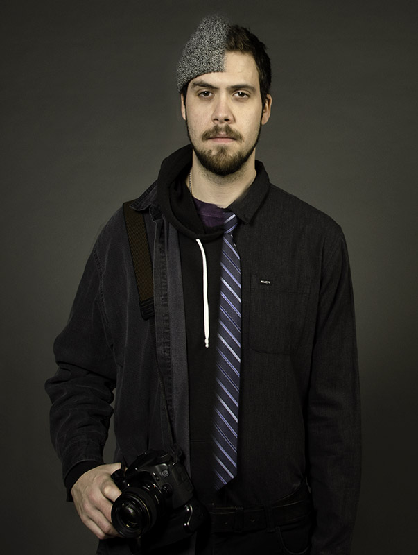 A portrait shot of Adam with half of him in professional cloths and the other half in regular clothes with a camera