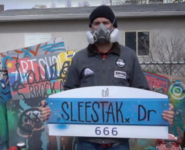 A man holding a street sign while wearing a gas mask.