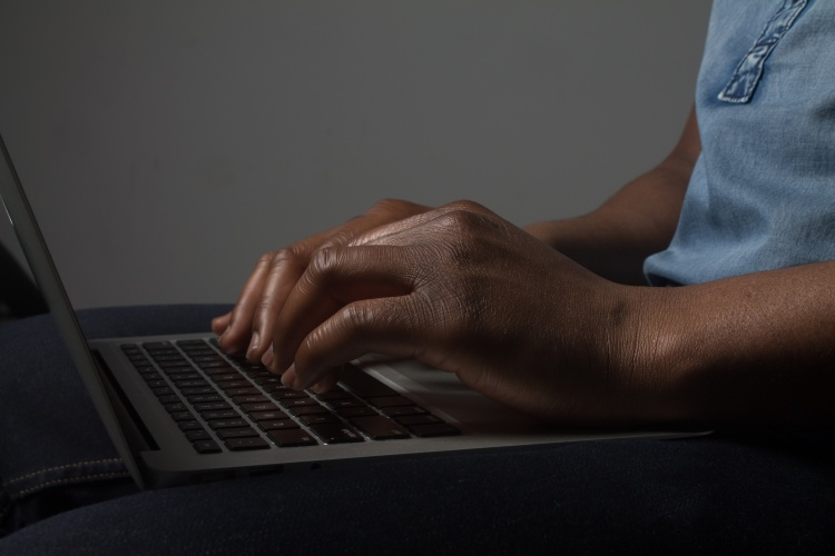 Close up of hands typing on a laptop keyboard.