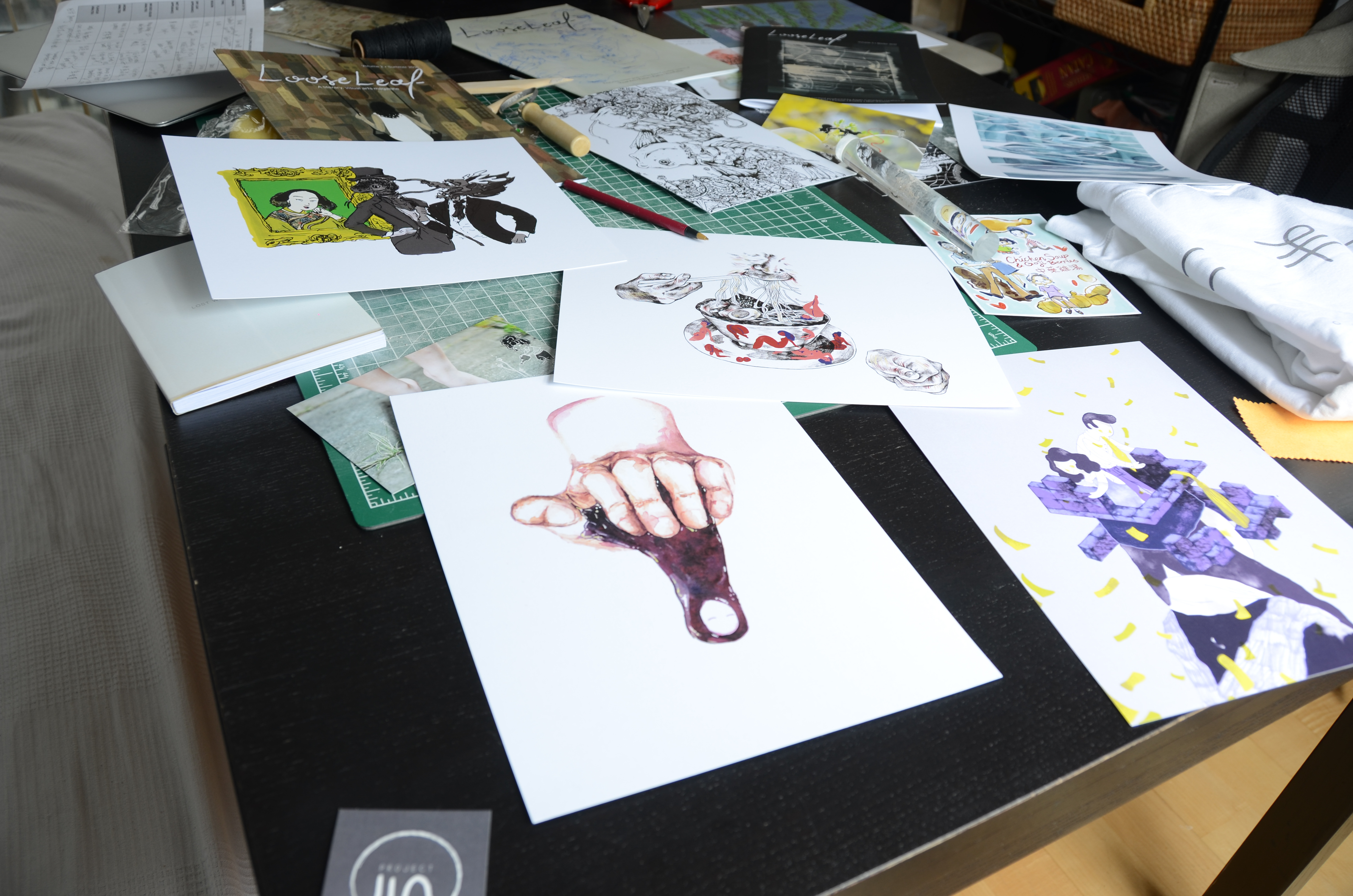 Close up a hand drawn images scattered over a desk.
