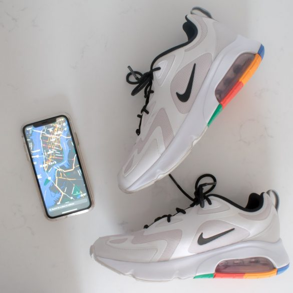 An overhead view of a pair of Nike sneakers set aside an iphone displaying a map on its screen