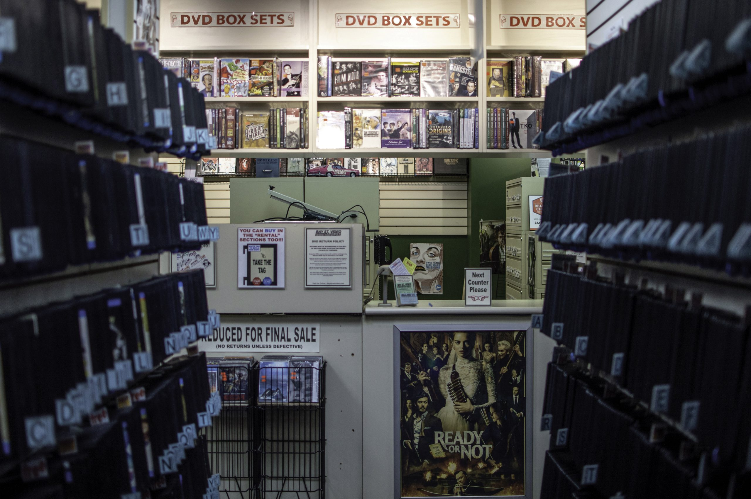 Wide shot of video store aisle revealing a counter